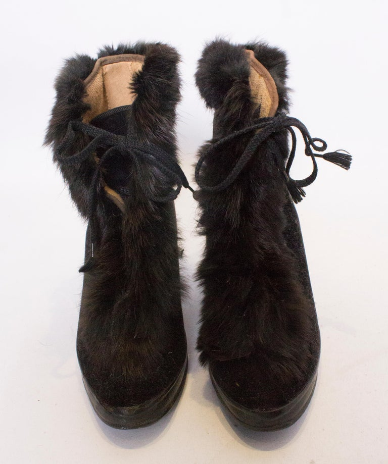 An unusual pair of fur trimmed over shoes. These are great for wearing with you evening shoes as the heel is hollow . Best size for a UK 5 1/2 - 6 1/2,.