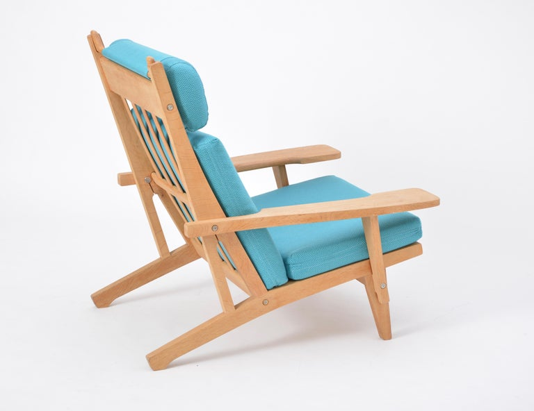 Turquoise Mid-Century Modern GE 375 Easy Chair by Hans J. Wegner for GETAMA   This easy chair is a version of the GE 375 model with armrests and a high backrest that Hans J. Wegner designed for GETAMA in 1969. The frame is made from oak; the loose