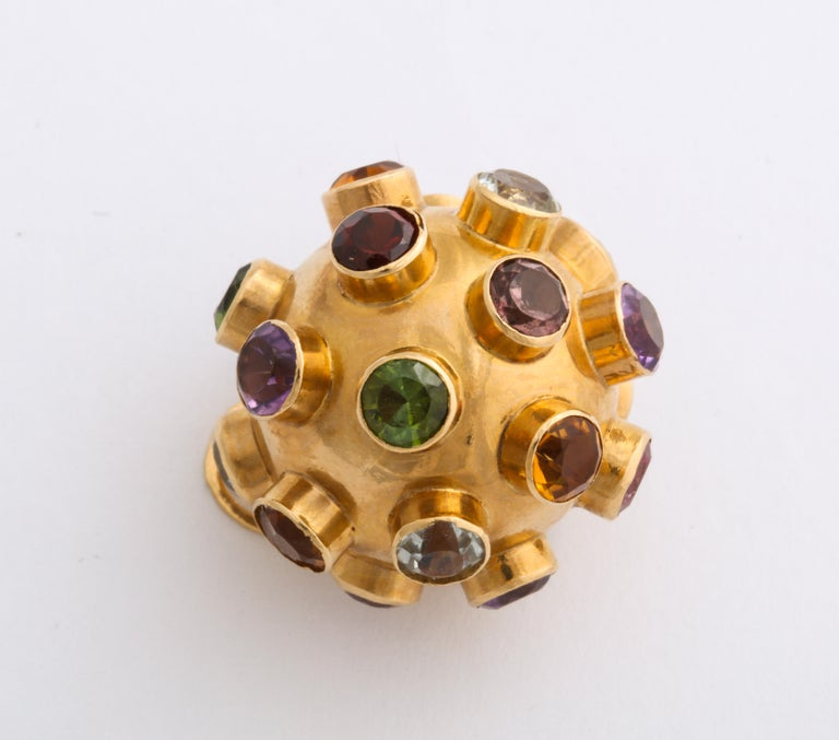 In 18 Kt, this pendant or charm, a gem studded ball, is set with colors true to their calling, garnet, aquamarine, citrine, amethyst, sapphire and green tourmaline. The stones are deeply set, each in their own collet. Sputnik, the first artificial