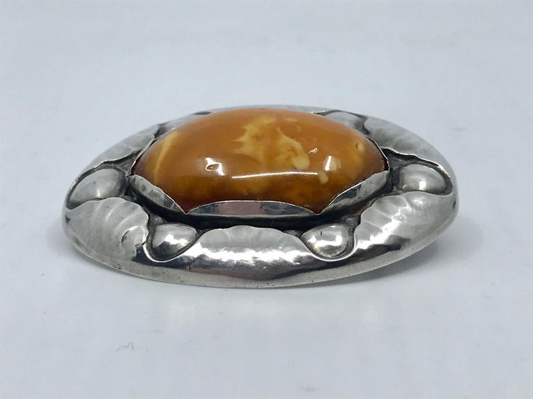 Rare vintage silver Georg Jensen brooch with a large oval amber stone, design #119 by Georg Jensen from circa 1913. Measures 2 1/8 x 1 5/8″ (5.5cm x 4.2cm). Vintage Georg Jensen hallmarks from 1915-1919, 830s.