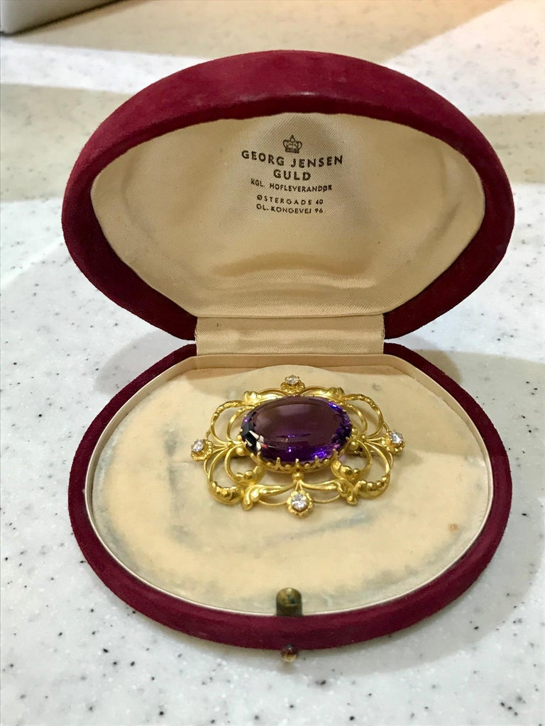 This is an 18kt gold Georg Jensen Art Nouveau brooch with a large oval cut amethyst stone and four small diamonds, design #21 by Georg Jensen. The diamonds are VS2.SI1 and are combined approximately 0.25ct.  The brooch measures 2
