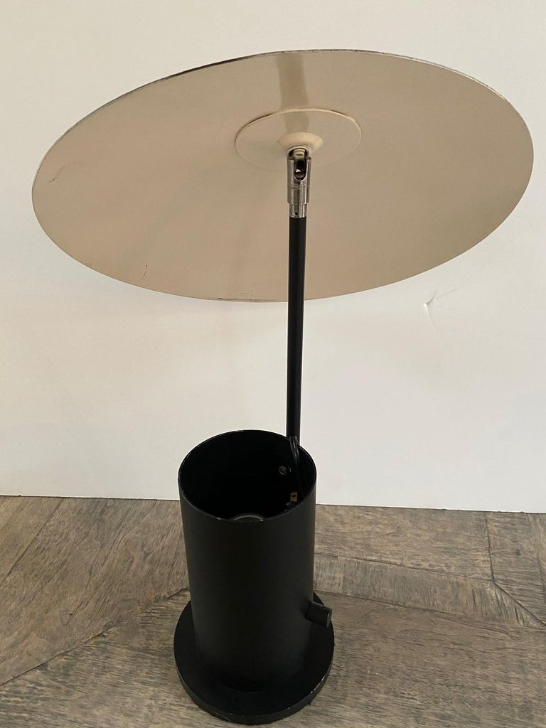 20th century enamel metal geometric modern table lamp, adjustable shade, light bulb sits in a cylindrical base design.