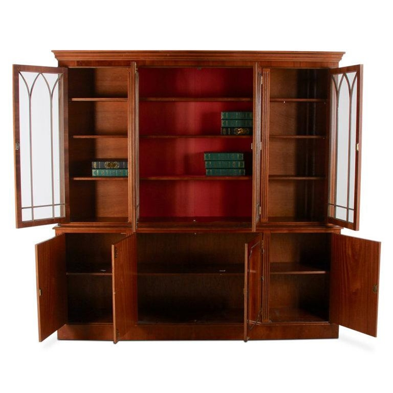 A vintage Georgian-style eight-door bookcase with four upper glazed doors and adjustable shelves and four lower cabinets.