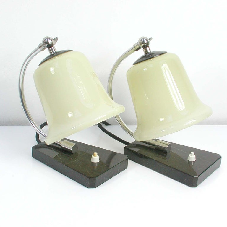 These table lamps were manufactured in Germany during the Bauhaus era in the 1930s. They have got a black marble base and a chrome lamp arm with adjustable opaline glass lamp shades.  Condition is very good with just minor signs of use and some