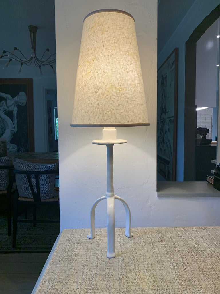 Inspired in a tribal design, this Giacometti style plaster over iron lamp with original shade.