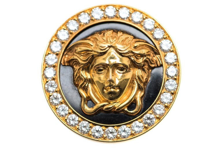 A vintage pair of 18 karat yellow gold earrings by Gianni Versace. Central cameo of Medusa on a black enamel background with a border of brilliant cut diamonds. Post and clip fittings. SignedGIANNI VERSACE 18K 750 and numbered 019. Measures 30mm
