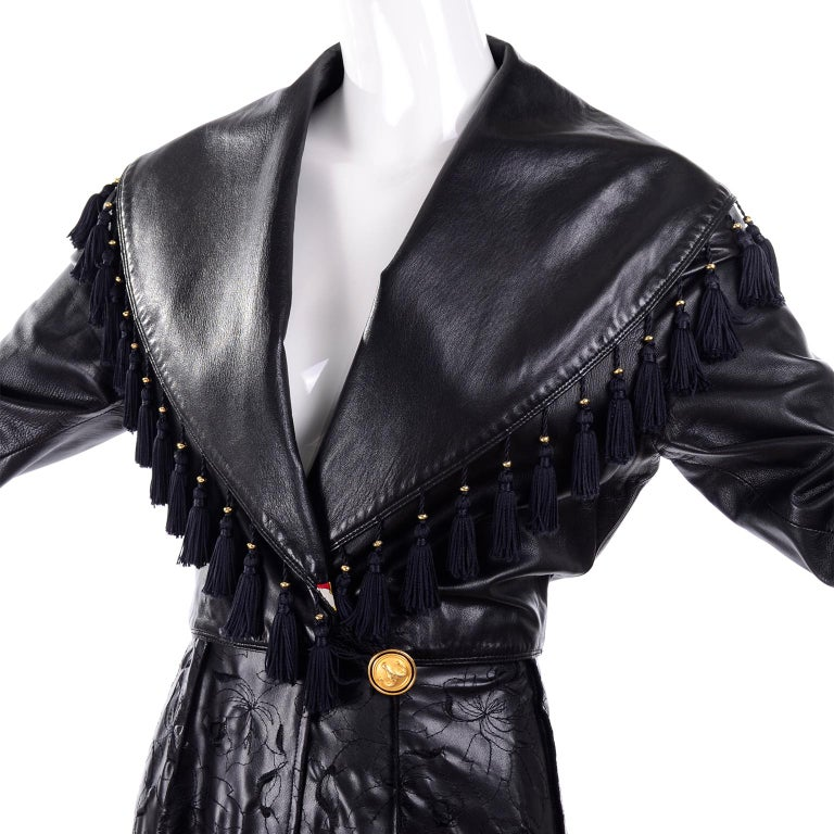 This is a very unique vintage Gianni Versace Coat in black leather with tassels. The coat closes with a ram's head button on the outside and gold medusa head button on inside. The bottom portion of the coat is embroidered leather with reverse seams