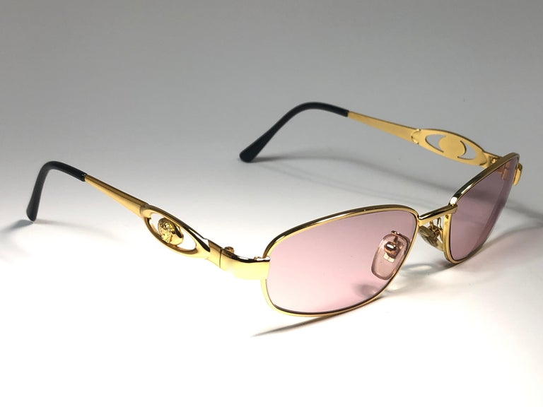 Vintage Gianni Versace small gold frame with rose lenses.   This pair show minor sign of wear due to storage.  Made in italy.
