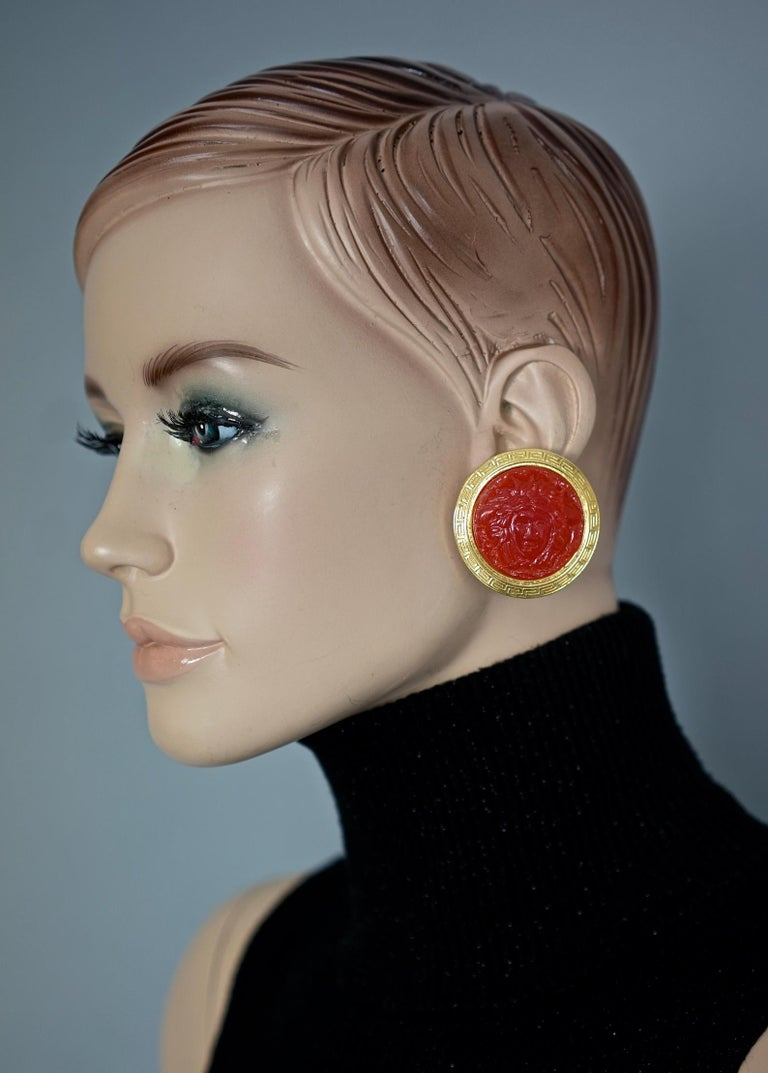Vintage GIANNI VERSACE Red Medusa Greek Keys Medallion Disc Earrings  Measurements: Height: 1.69 inches (4.3 cm) Width: 1.69 inches (4.3 cm) Weight per Earring: 23 grams  Features: - 100% Authentic GIANNI VERSACE. - Red Medusa head at the centre