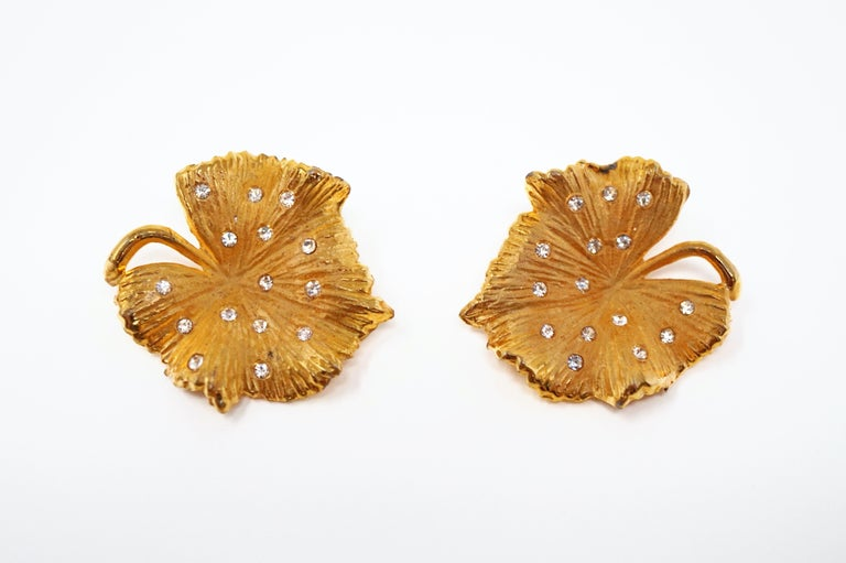 These rare, shiny statement earrings by Claudette, circa 1950s, are a great way to add a touch of sparkle to your look!  Two gold-plated leaves are studded with sparkling crystals in these gorgeous clip-on earrings. A wonderful addition to your
