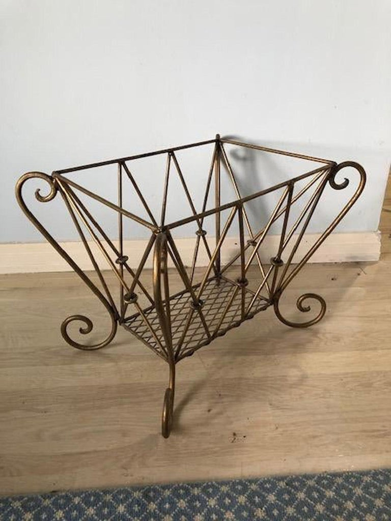 The vintage Hollywood Regency style magazine rack is made of gilt metal designed with a flare. Add a liner and it could become a log/kindling basket. Potted plant stand?