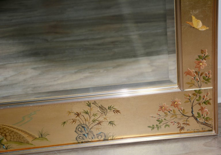 We are offering a vintage Labarge painted gilt chinoiserie style wall mirror. This mirror features a large bevelled glass mirror framed by panels of glass with painted in gold with hand-painted natural, figural, and architectural motifs in greens,