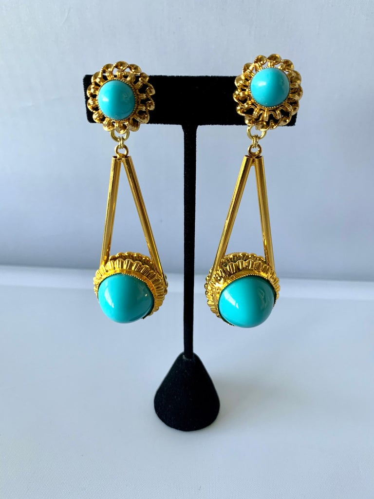 Vintage architectural chandelier clip-on earrings comprised out gilt-metal adorned by large turquoise glass cabochons, designed by William de Lillo circa 1970.