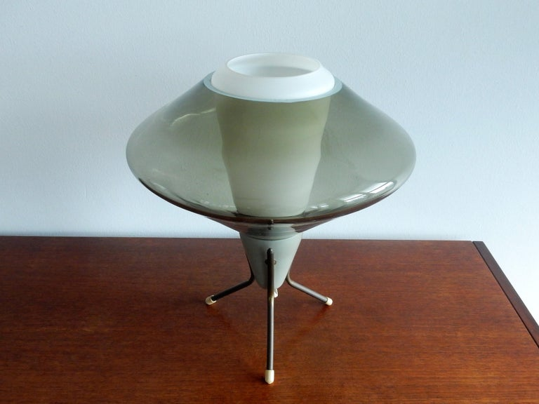 This is a nice tripod table lamp made of metal, opaline and green smoked glass. It has a futuristic Space Age shape and gives a very atmospheric and warm light. It is in a very good condition with some signs of age and use, as pictured. This design