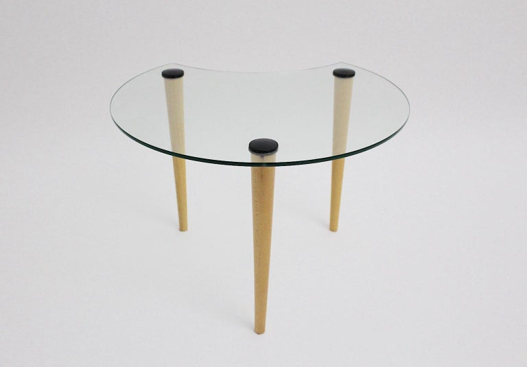 This vintage glass coffee table / side table shows a sickle-shaped glass top and three beech legs. The coffee table was designed and made in the 1970s in Italy. The vintage condition is very good. Approx. measures: Diameter 60 cm Height 42 cm.
