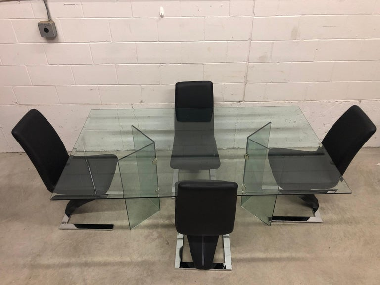 """Vintage glass rectangular dining table with glass base and four zig zag vinyl Rinaldi-style dining chairs with chrome steel bases. The chairs measure 17"""" L x 18"""" W x 37.5"""" H, the seat is 19"""" H. The chairs are in excellent condition. The table has"""