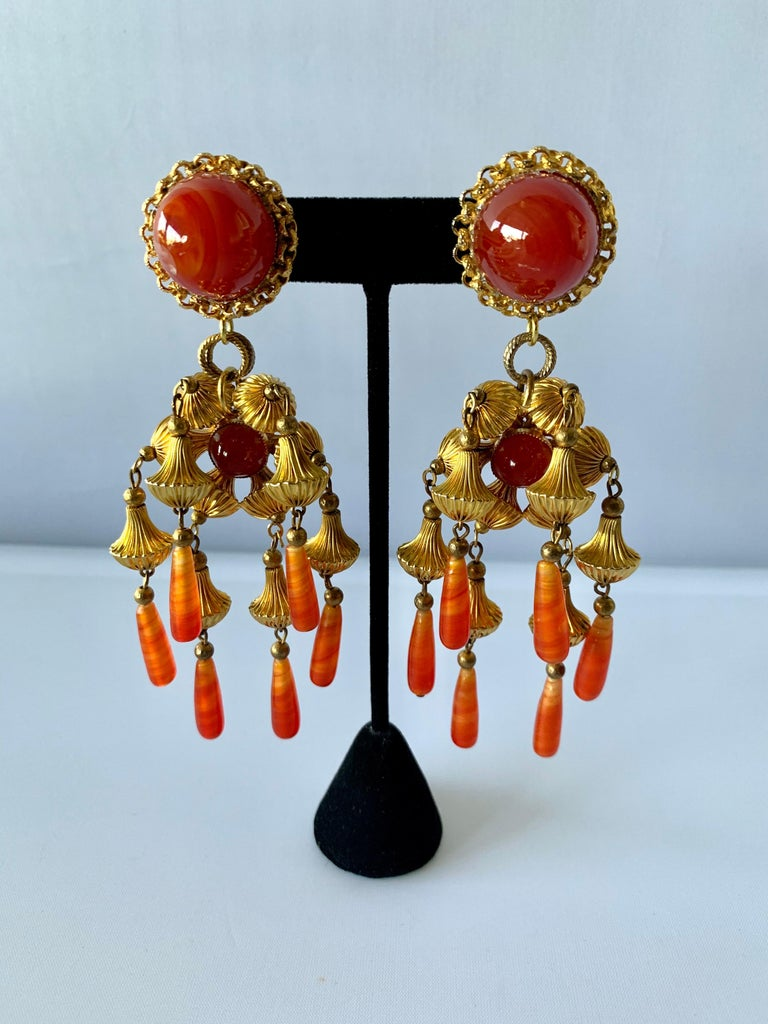 Vintage mid-century statement clip-on earrings comprised out of ornate gilt-metal beads and faux glass carnelian cabochons. The earrings have an oriental design, designed by William de Lillo circa 1969.