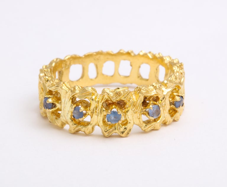 The heavens touch this 18 Kt gold band by setting twinkling blue Ceylon color sapphires around the lacelike face. The sapphires are small stones with few facets, no more than 3.5 points total weight yet their presence is just right for the space