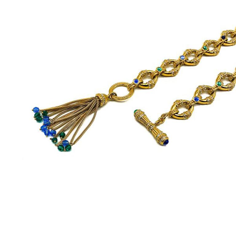 A striking Vintage Jewelled Tassel Sautoir. Crafted in high quality gold plated metal set with cabochon and faceted green and blue glass stones with clear rhinestone chaton accents. Featuring intricate craftsmanship throughout the necklace is