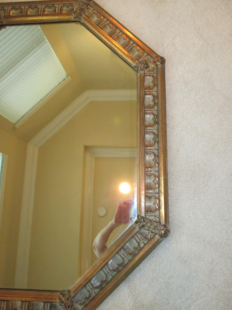 Beautiful gold wooden octagonal mirror with floral accents. Hanging hardware is attached.