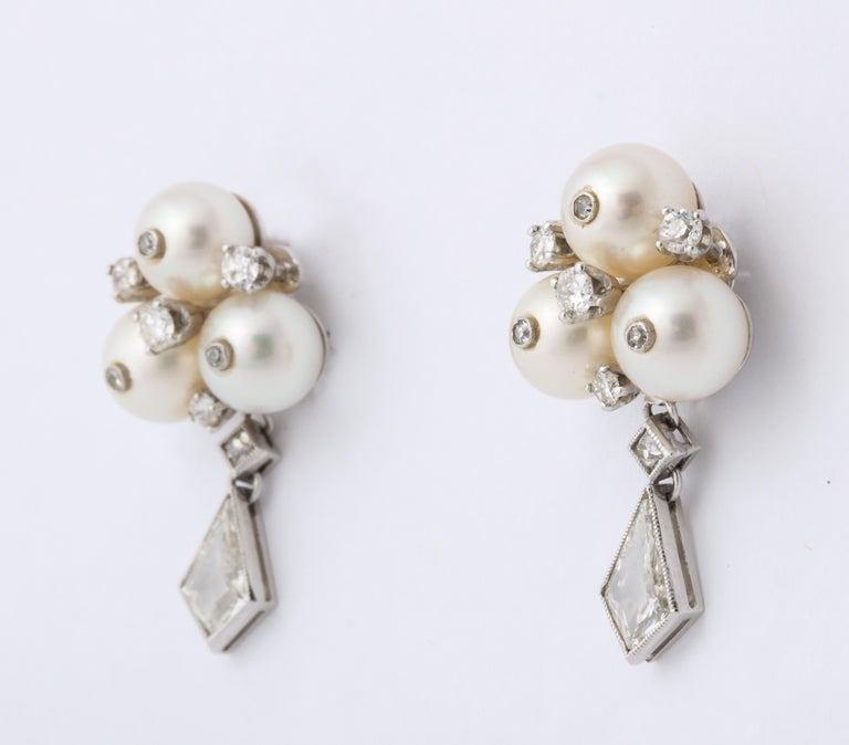 Unusual kite shaped diamonds twinkle wand move on this pair of vintage 6 mm cultured pearl earrings, with diamond flecks inset on each pearl. Between each pearl, east, west, south and central sits another diamond, all stones modern, brilliant and