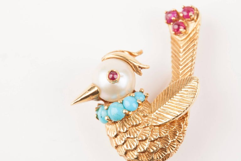 Very charming Bird brooch. The head is made with a beautiful akoya pearl.  The brooch is made of 18k gold, set with turquoise and rubies. French made circa 1960. Marks of the maker. Made circa 1960. Heights: 4cm width: 2.2 cm Weight: 9 grams