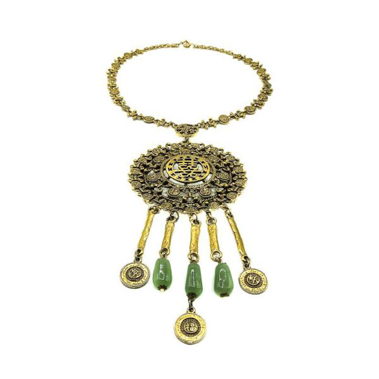 A stunning larger than life Vintage Goldette Chinese Medallion Necklace. Crafted in gold plated metal and with glass faux jade beads on the droplets. Goldette designs are typically highly detailed and whimsical. Drawing upon a myriad of influences