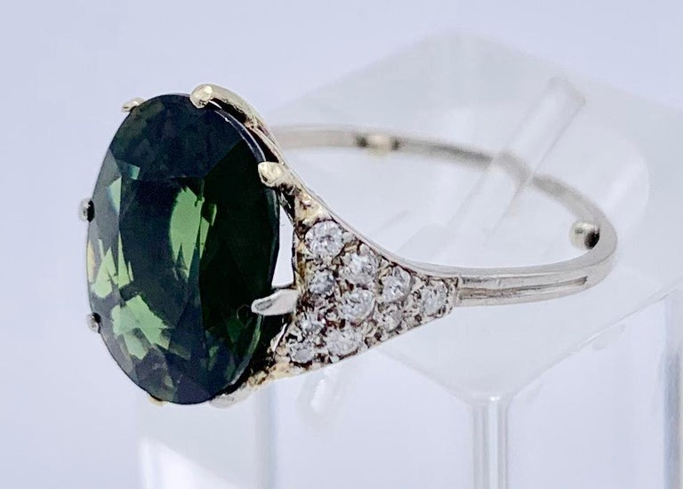 Lovely oval green faceted sapphire, mounted in a very elegant platinum setting together with small diamonds. Very wearable, has been made around 1950.  Ring Size US 5.5