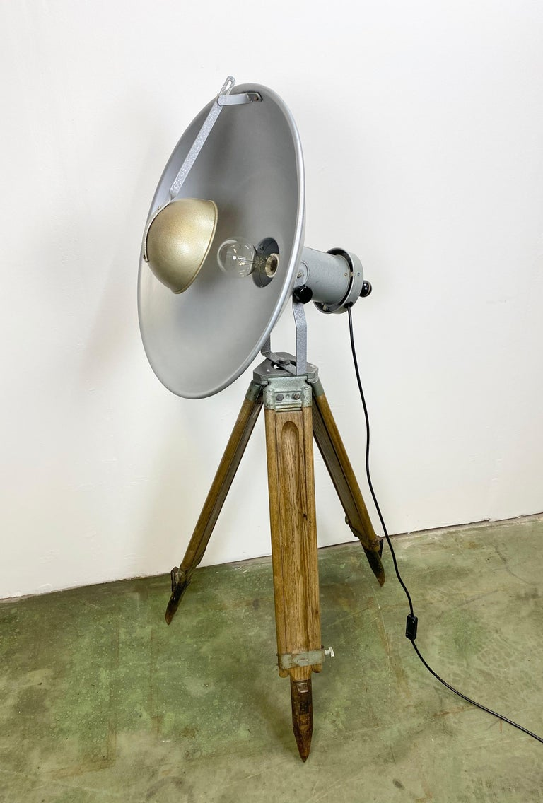 - Industrial lamp on wooden tripod - Made by Mechanika Praha in former Czechoslovakia during the 1960s - Adjustable height and angle - Grey hammerpaint metal body  - New porcelain socket for E 27 lightbulbs - New wire  Additional dimensions: