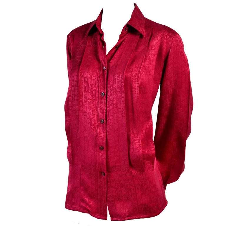 This is a gorgeous Gucci silk blouse in a deep red with the Gucci G logo signature in the tone on tone print.  This early 1980's blouse also has Gucci written on the buttons up the front. These Gucci silk blouses are so well made and they are always
