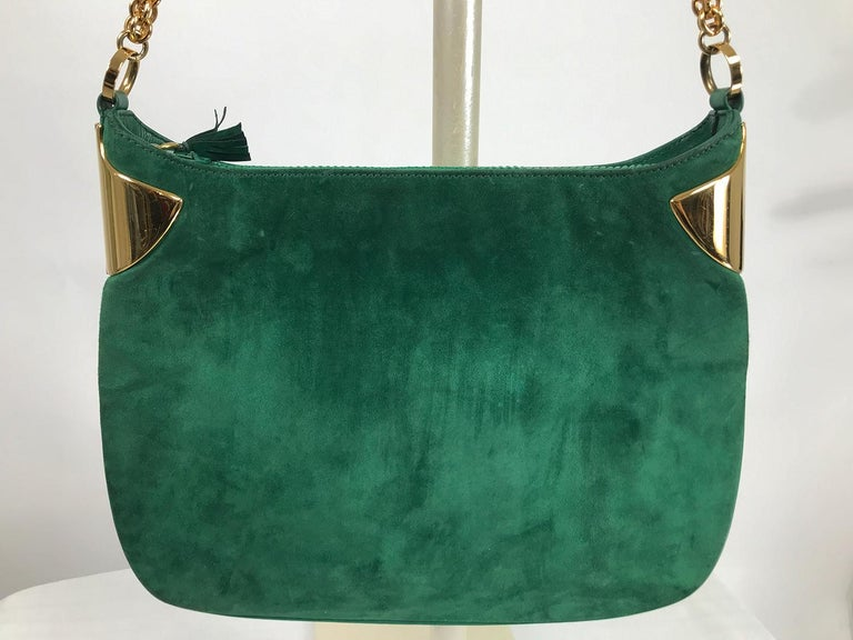 Vintage Gucci forest green suede with heavy gold chain shoulder strap and gold hardware from the 1980s. This beautiful bag is sleek and modern, with it's chunky gold chain and compact shape. Suede bag with leather trim and sides, the bag has a