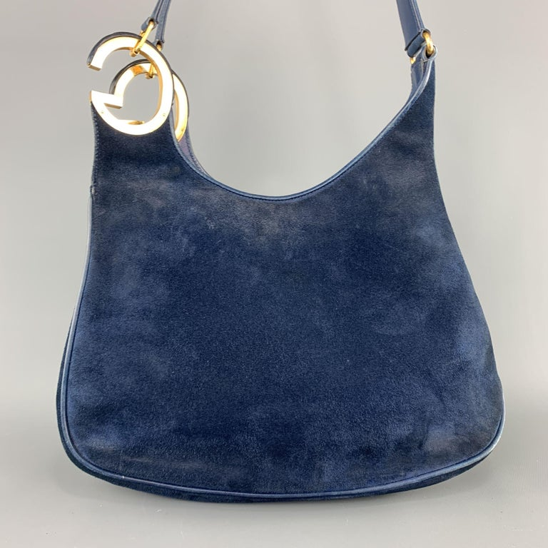 Vintage 1970's-1980's GUCCI shoulder bag comes in navy blue suede with leather piping, yellow gold tone metal hardware, and double oversized GG metal accent. Wear and aging throughout leather and suede. As-is. Made in Italy.  Good Pre-Owned