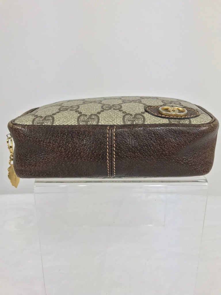 Vintage Gucci small leather and monogram vinyl cosmetic bag...Oval leather applique with metal intertwined G's at the front, the bag is pigskin leather at the sides, top and bottom...Lined in brown vinyl...Some wear but basically in very good usable