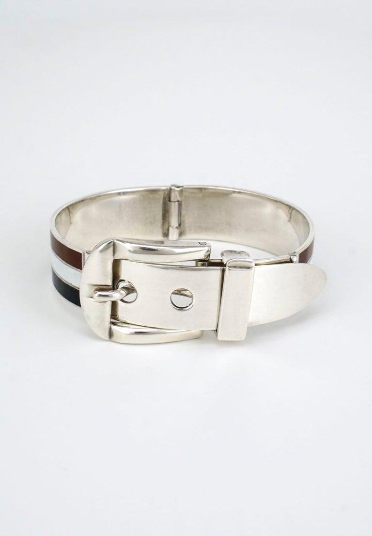 An iconic Gucci sterling silver hinged bracelet of two panels of three stripes with a central white stripe bordered by brown and black stripes with a hinged working buckle and three hole hinged belt tip - marked for Gucci Italy, sterling and a pre
