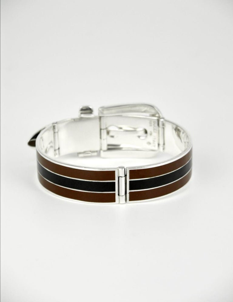 An iconic Gucci solid silver black and brown enamel belt bracelet consisting of two hinged panels each decorated with three stripes with a central black stripe bordered by brown stripes with a hinged working buckle and three hole hinged belt tip -