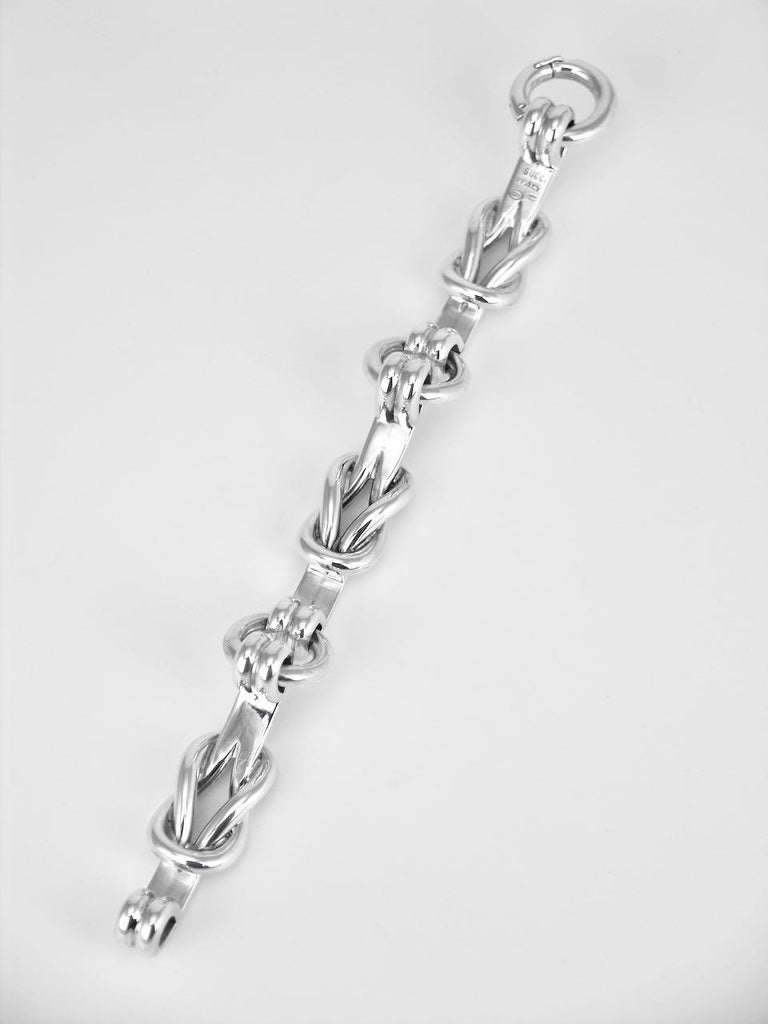 This designer solid silver heavy bracelet is made up of three panels of a Hercules knot and linked with large round links with an integrated split link clasp with safety clasp.  This iconic design with a nautical flavour is very rare to find and