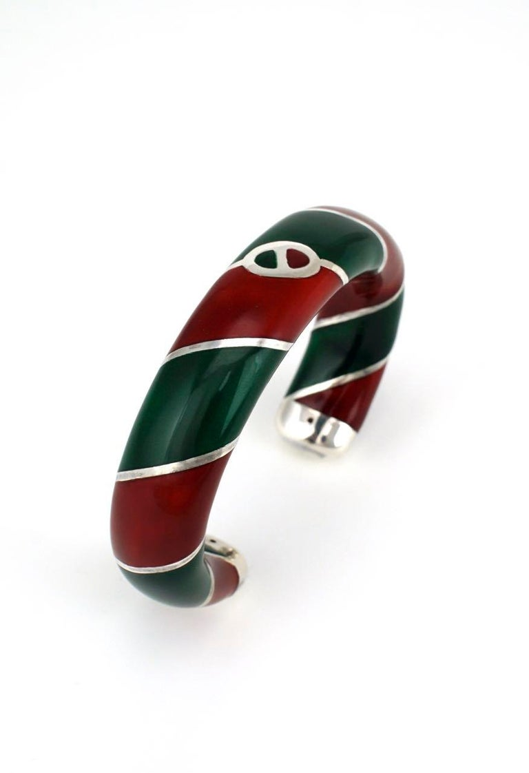 A striking Sterling silver hollow tubular cuff with wrapped stripes of red and green enamel with a central Gucci link logo.  This Designer bangle in the iconic Gucci colours is presented in its original Gucci green fabric presentation box - marked