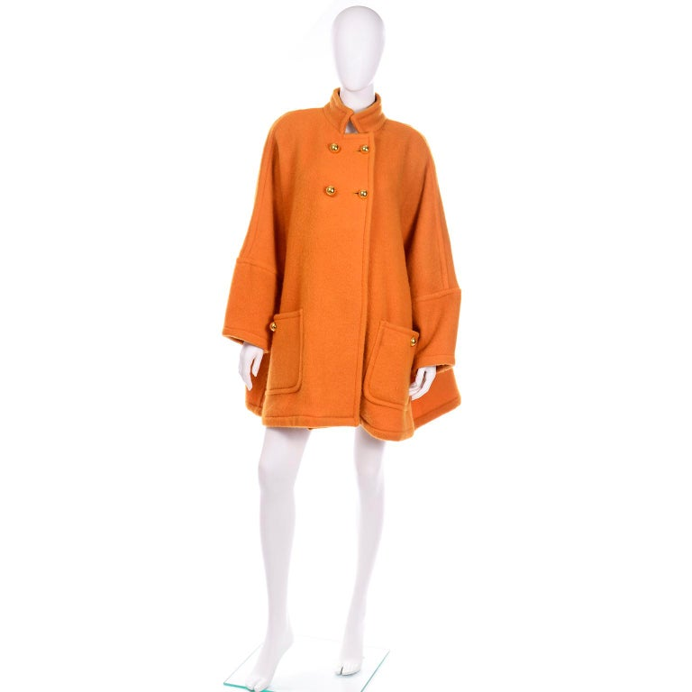 This vintage Guy Laroche coat is in a tangerine shade of orange mohair and wool blend with round dome gold buttons. There are two functional front pockets with gold button closures and shoulder pads for structure. The batwing sleeves add so much