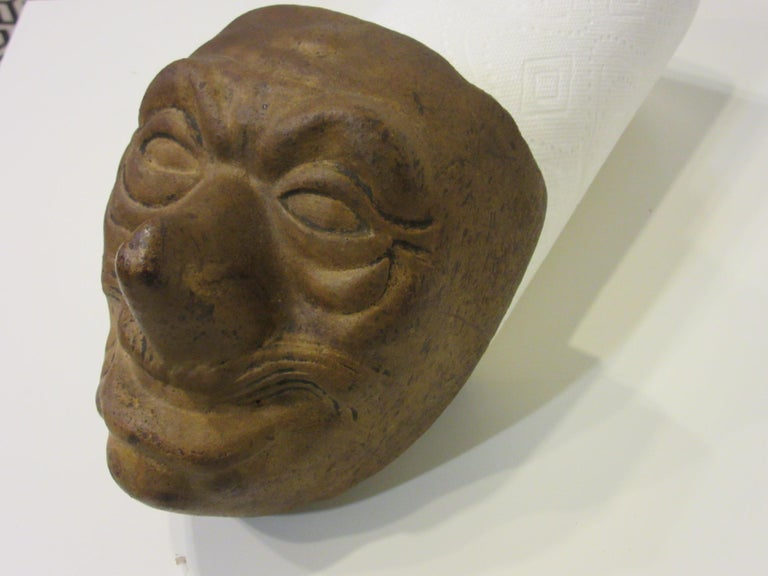 A handcrafted 1920s fired brick mask mold used in making gauze styled Halloween masks by wrapping the mold, hand painting the face and waxing the front and back after drying to set the piece for wearing. This was an early method in mask making and