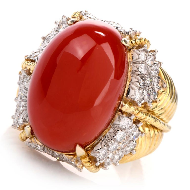 This bold circa late1970's Hammerman Brithers ring is crafted in solid 14-karat yellow gold, weighing 22.9 grams and measuring 23mm x 17mm high. Centered with one prong-set oval natural red coral weighing approx. 19.30 carats measuring 20mm long x
