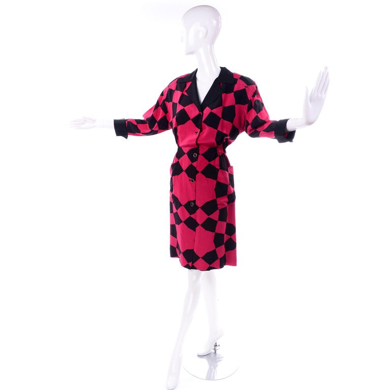 This is a red and black abstract harlequin pattern silk dress designed by Hanae Mori.  The dress has two hip patch pockets with a notch out of the top, deep purple buttons with gold trim and shoulder pads. There are and 3/4 length cuffed button