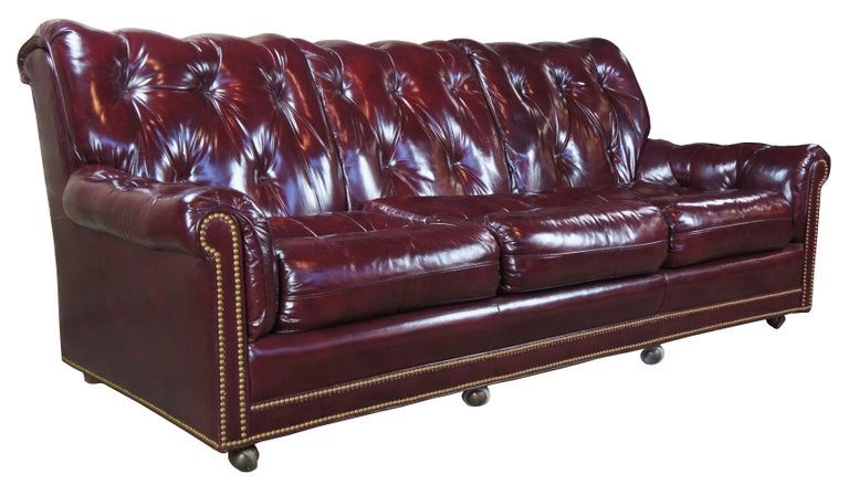 Vintage Hancock & Moore top grain leather sofa. Features a burgundy or dark red tufted leather and plush rolled back with brass nailhead trim, circa 1980s. On castors for ease of movement. Measure: 87