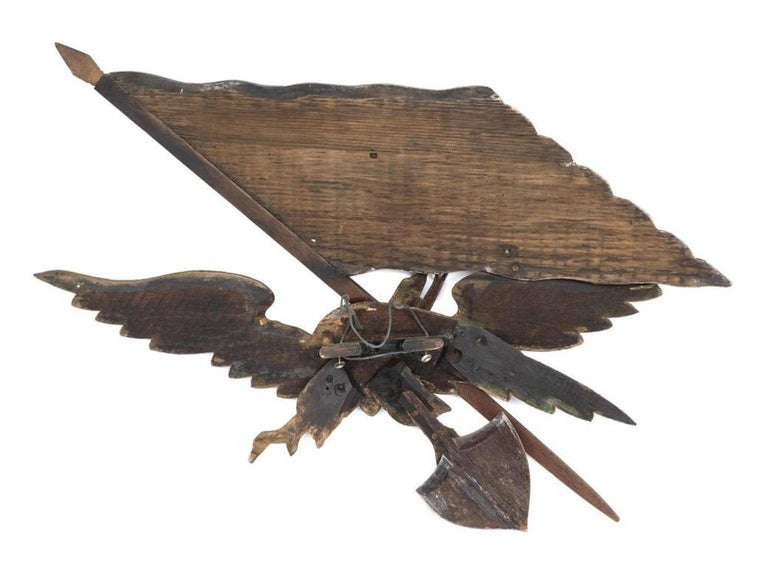 Presented is an antique hand carved eagle by George Strapf. Painted and parcel-gilded, this wood eagle is a stellar example of American Folk Art at the turn of the 20th century. The eagle clutches a shield in its dexter talon and supports an