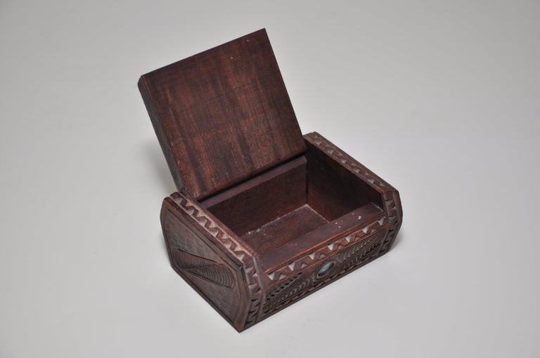 Vintage hand carved shell eyes wooden box, a vintage hand carved and inlaid dark wooden trinket or jewelry box decorated with a Maori tribal face and inlaid paua shell 'eyes' on the pin-hinged lid, with other incised motifs to the sides. This is an