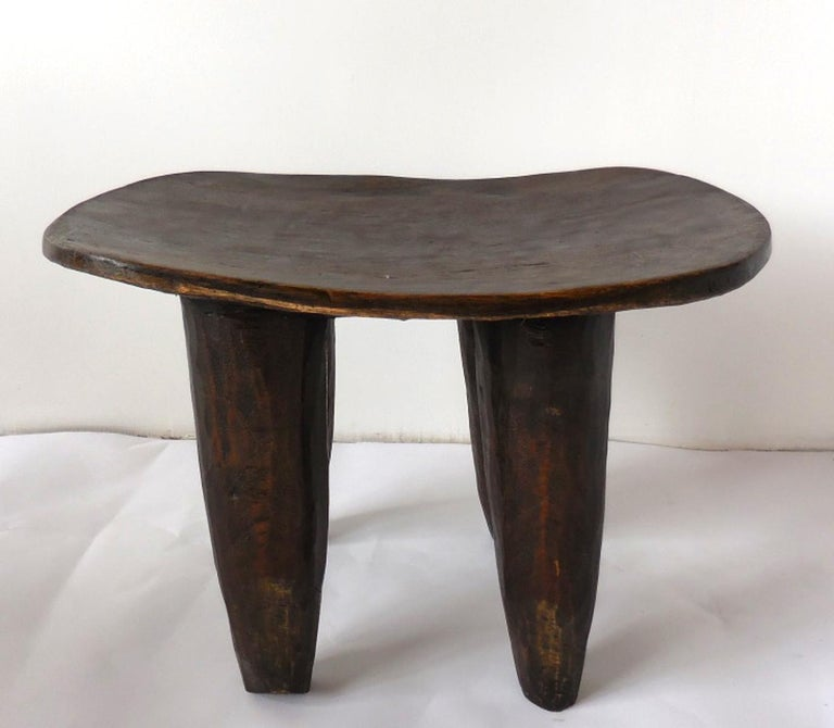 Carved out of one piece of wood, this is a traditional tribal stool from the Senufo tribe in Mali. Conical legs and slightly undulating top. Soft worn patina. Can be used as a stool or a side table.