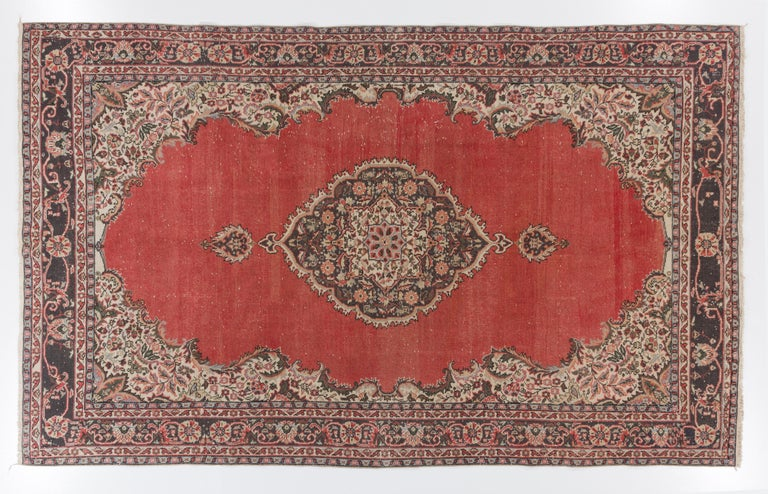 A fine vintage hand knotted Turkish Oushak rug from the 1960s featuring a central floral medallion in dull navy blue against a plain warm madder red field, finished off with spandrels in cream and a border in olive green and navy blue both filled