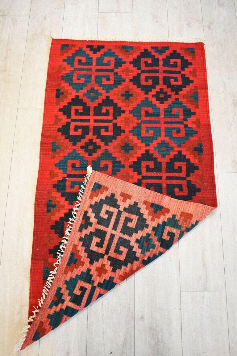Beautiful handwoven vintage Kilim runner with geometric pattern Naturally dyed wool in shades of red, black and navy.