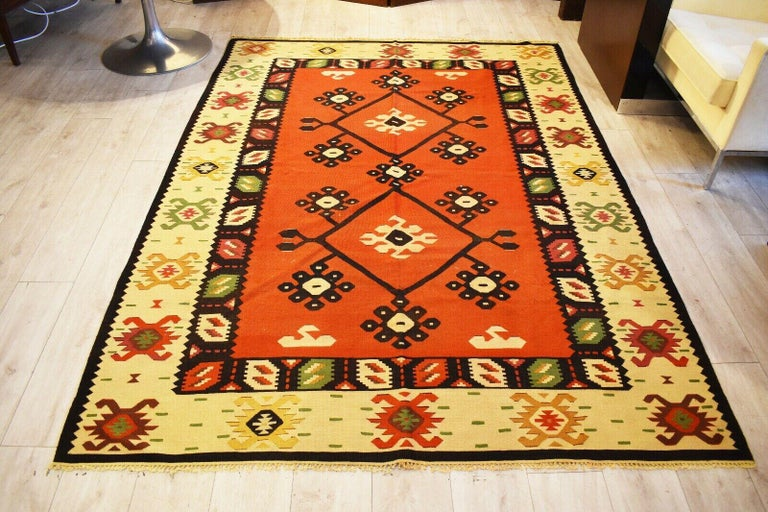 Beautiful handwoven vintage Kilim runner with geometric pattern Naturally dyed wool in shades of red, green and natural straw tones.