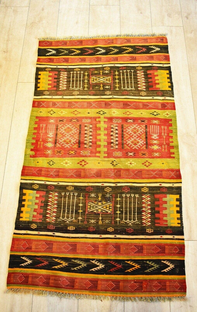 Very rare and unusual beautiful handwoven vintage Kilim runner with patterns in shades of natural dyed red, black, yellow and green colours. Handwoven with natural dyes. Has a lovely aged patina & nice quality.