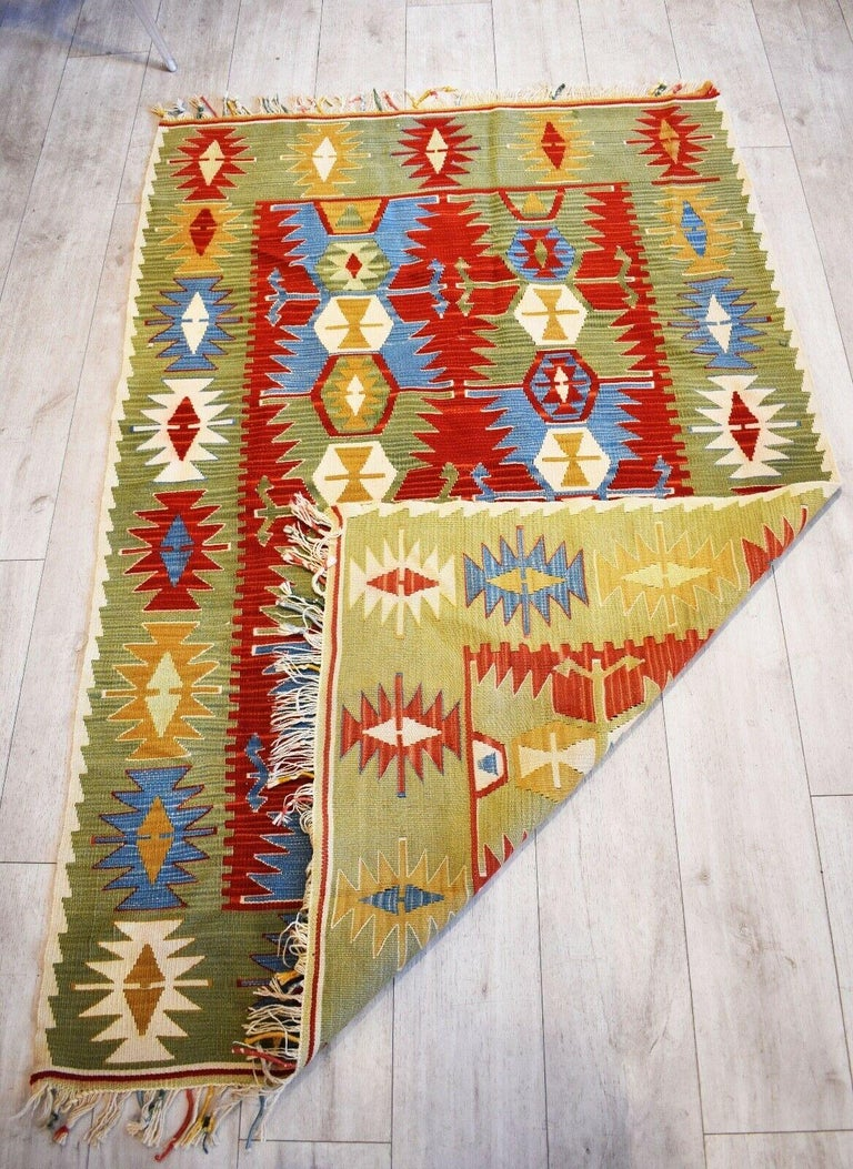 Very rare and unusual beautiful handwoven vintage Kilim runner  with patterns in shades of  paprika red, deep sky blue, buttercup yellow on an avocado green coloured background  with a beautiful tasseled edges.  Handwoven with natural dyes Has